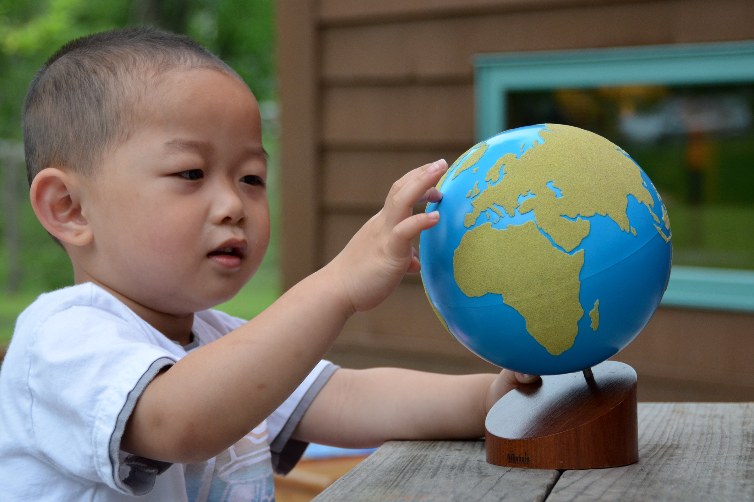 Child using sandpaper globe