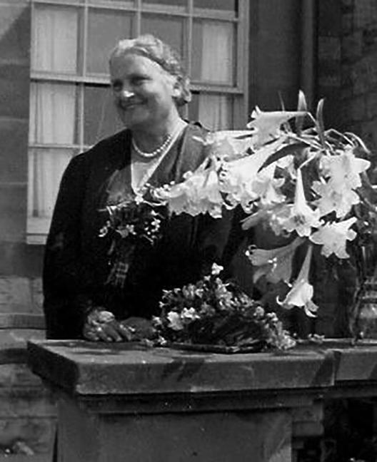 Maria Montessori outside with flowers